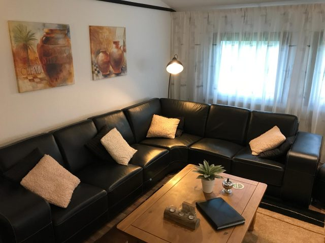 Een grote woonkamer, voorzien van voldoende zitgelegenheid